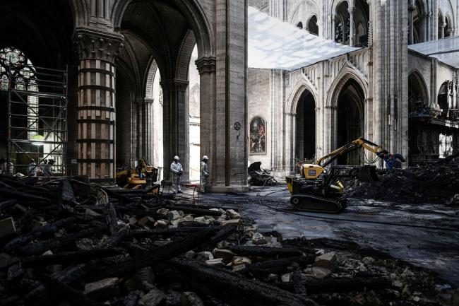 Workers stand near damages and rubble during preliminary work inside the Notre Dame de Paris Cathedral, Wednesday May 15, 2019 in Paris. French Culture Minister Franck Riester says that one month after a fire engulfed Notre Dame Cathedral, the edifice is